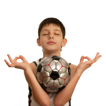 A kid is meditating holding a football ball in his arms